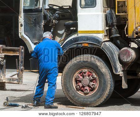 Worker mechanical repairing dirty truck. Service maintenance.
