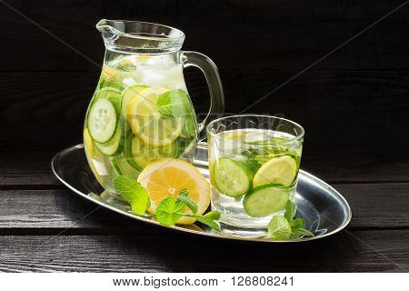 Fresh cold water with lemon cucumber ginger mint and ice in a pitcher and a glass on a metal tray