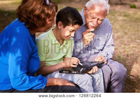Grandparents educating grandson: Senior woman and old man spending time with their grandchild in park. The old people help the boy studying and doing school homework. The kid holds a tablet pc