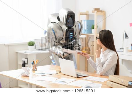 Here you are.  Cheerful content charming girl sitting at the table and  smiling while the robot giving her papers