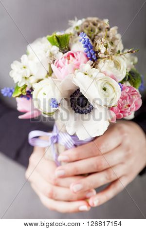 Woman in grey dress and black shirt is holding in her hands a spring bouquet from pink tulips violet grape hyacinths white anemones violet veronica and white buttercup with violet ribbon