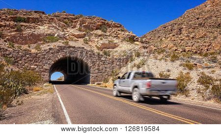 Car drives through a stone tunnel in Big Bend National Park Texas