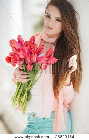 Young beautiful woman brunette with long straight hair and brown eyes,dressed in a beige jacket and a white t-shirt, wears around his neck beige scarf, posing for the photographer in the summer outdoors with a bouquet of red tulips