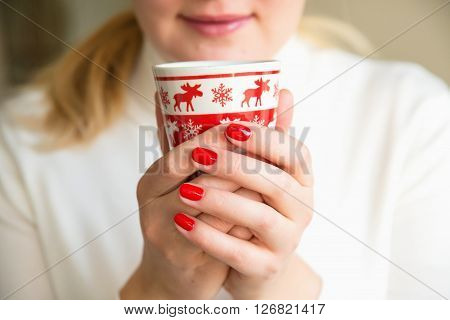 Close up of hands with a cup. Protect your health. Drink herbal tea. Woman holding a red cup of hot drink. Drink hot tea or coffee in the morning cool. Traditional autumn or winter warming drink.