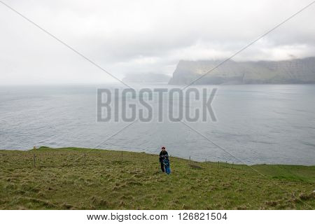 People hiking on the Faroe Islands on the island Kalsoy with Vidoy in the background