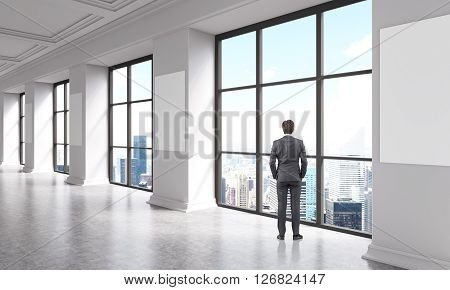 Concrete interior with blank posters on columns and businessman looking out of window with New York view. Mock up 3D Rendering