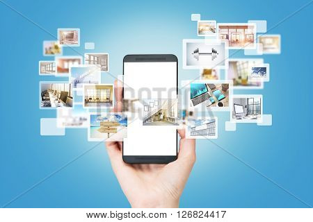 Hand using smartphone for site surfing. Different icons with pictures appearing from the screen