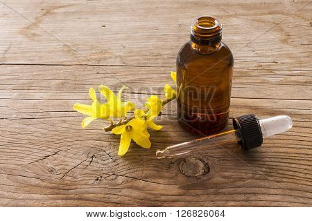 close-up of essence of forsythia on wooden table