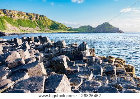 Giants Causeway unique geological hexagonal formation of volcanic basalt rocks and cliffs in Antrim County Northern Ireland in sunset light