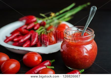 Glass jar of homemade tomato sauce with fresh ingredients on dark wooden background. Natural homemade sauce of tomatoes, peppers and vegetables. Fresh Homemade Salsa Dip. Selective focus.