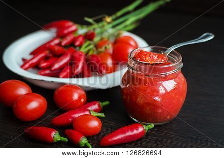 Glass jar of homemade tomato sauce with fresh ingredients on dark wooden background. Tomato ketchup sauce with cherry tomatoes and mini red hot chili peppers. Selective focus.