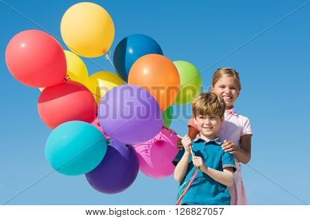 Cute boy and girl playing with colorful balloons outdoor. Happy smiling children looking at camera with balloons. Happy sister and brother having fun with balloons with blue sky in background.