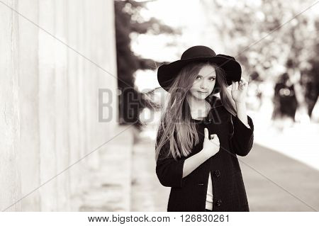 Stylish teenage girl 14-15 year old wearing trendy coat and hat outdoors. Looking at camera. Fashionable.