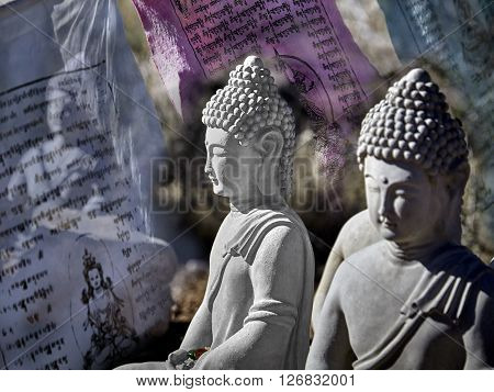 Buddhist figures made of cement sitting in meditation with prayer offerings and prayer flags