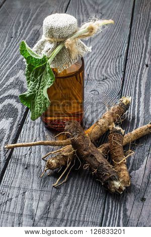 Medicinal plant - a burdock. The roots and leaves of burdock burdock oil in bottle on a wooden background. It is used for the treatment and care of hair