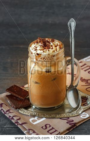 Glass of thick creamy coffee milkshake, frappe or iced coffee with a topping of ice cream and drizzled chocolate