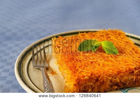 Turkish Kataif cake on a plate, close up