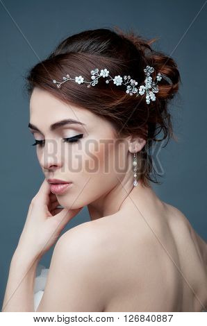Bridal fashion hairstyle and makeup. Brunette bride in wedding dress and beaded headpiece.
