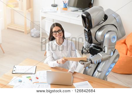 Like my job. Cheerful positive charming woman sitting at the table and looking up while getting package from the robot