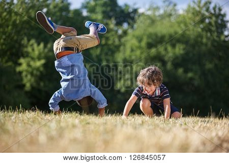 Two kids making a somersault and smiling in the nature