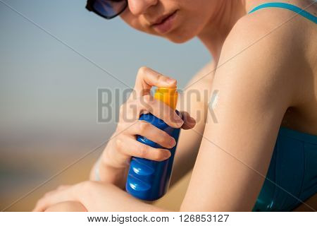 Spraying Sunscreen Lotion On Shoulder