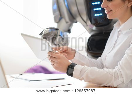 Just look. Delighted smiling beautiful woman sitting at the table and using tablet with robot who is standing nearby