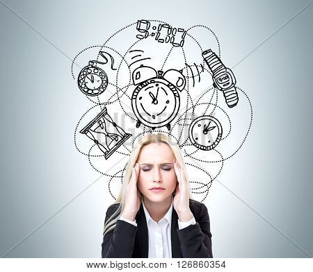 Lack of time concept with stressed businesswoman on grey background