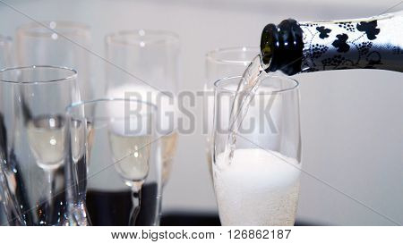 Spilling champagne into glasses. Festive alcohol from bottles. The flow of champagne in a glass flute. The dense foam of champagne.