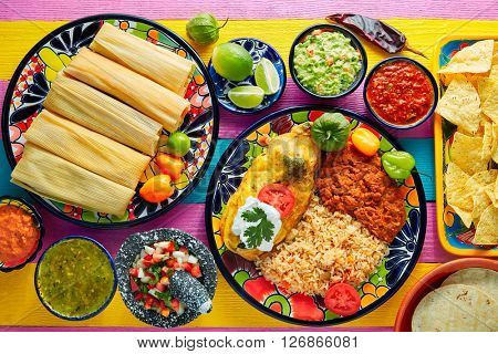 Tamale with corn leaf and filled chili pepper poblano guacamole  sauces