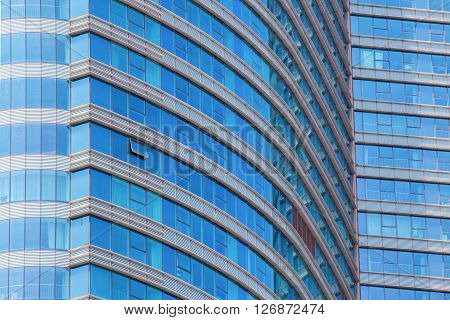 Front of an office building rounded with blue windows