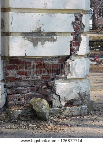 Old dilapidated stucco corner of building with red bricks in deep fissure
