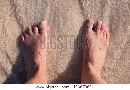 Feet in white sand by the ocean