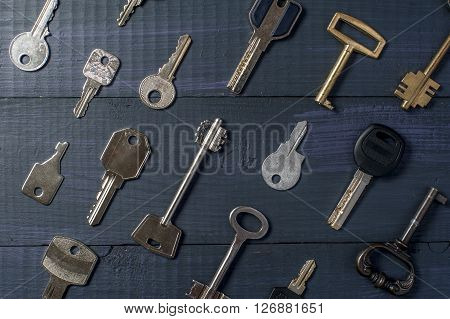 Many keys on wooden table, horizontal view