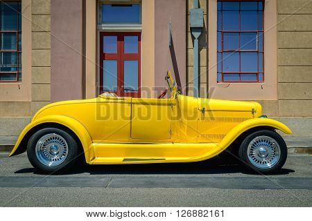Adelaide, Australia - February 9, 2014: Yellow custom hot rod parked on the street in Port Adelaide on a bright day. Australia has a very rich automotive culture