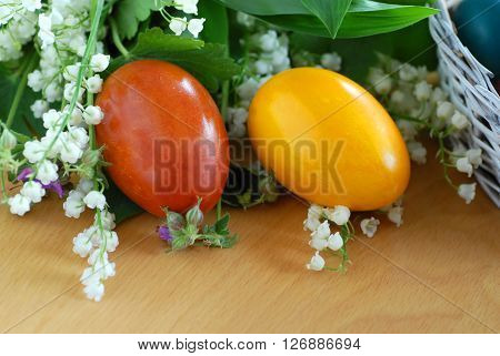 two brown and yellow easter eggs on the table with may-lily flowers
