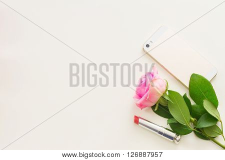 Styled desktop scene  with  mobile and pink flowers, copy space on white table