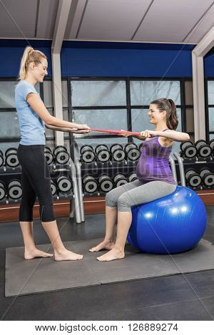 Trainer and pregnant woman using a resistance band at a gym