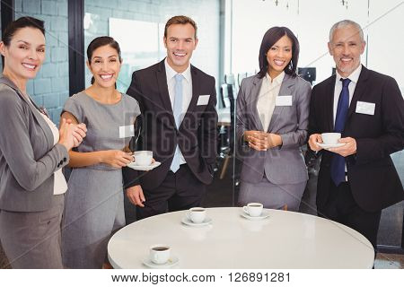 Portrait of businesspeople having tea during breaktime in office