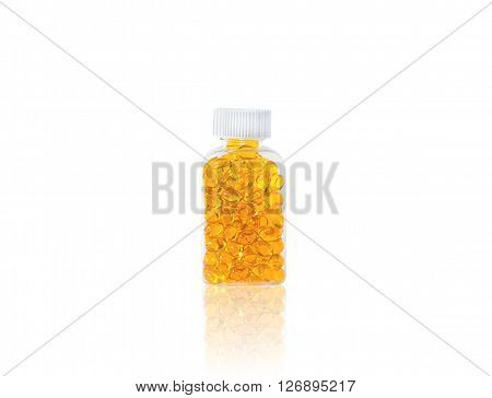 Omega 3 fish oil capsules spilling out of a bottle on a white background with reflection