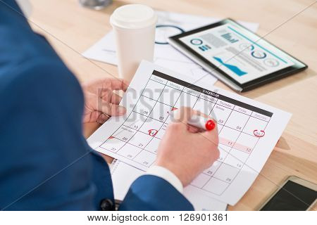 In pace with time.  Pleasant man sitting at the table and holding highlighter while marking dates in the calendar