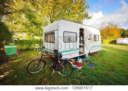 Caravan Trailer And A Bicycle On A Green Lawn Under The Trees, On A Sunny Autumn Day In France