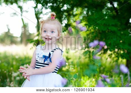 Laughing blonde girl 2-3 year old playing in meadow. Wearing trendy striped dress. Childhood.