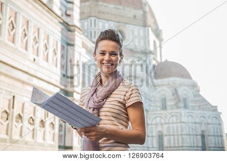An amble around awe-inspiring Duomo in Florence Italy. Portrait of happy woman tourist with a map listening to the audio guide poster