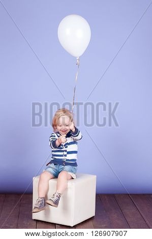 Child girl 2-3 year old holding white air balloon in room. Sitting on chair over purple. Wearing striped shirt and denim shorts. Playful baby. Childhood.