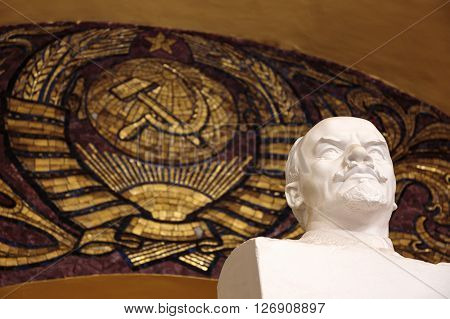 MOSCOW - MARCH 3: Lenin sculpture in Komsomolskaya metro station on March 3 2016 in Moscow. At the end of the platform is a bust of Vladimir Lenin under an arch decorated with gilt floral designs and the Coat of arms of the Soviet Union.