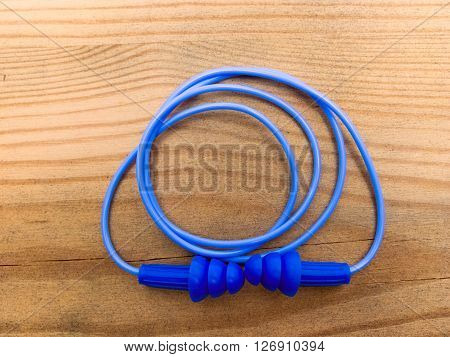 Ear plugs with cord lying on wooden background