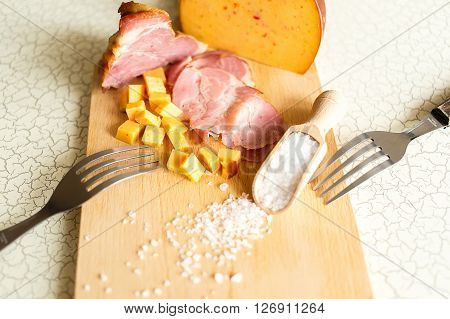 Ham cheese bread and salt on a wooden cutting board. The breakfast in the village. Snack with beer or nosh.