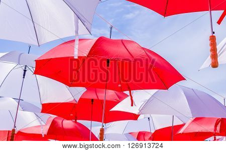 Hanging Multicolored umbrellas over blue sky. Red and withe large size umbrellas onto the blue sky.