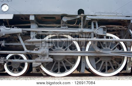 Details of the undercarriage of an old steam locomotive on railway tracks are shown.