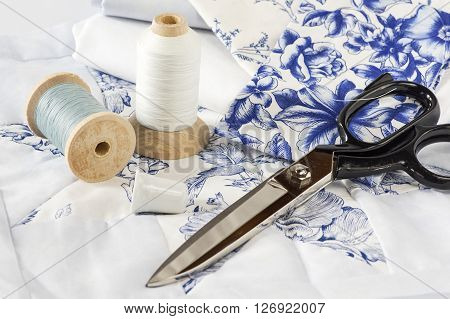Sewing accessories, fabric and thread on white